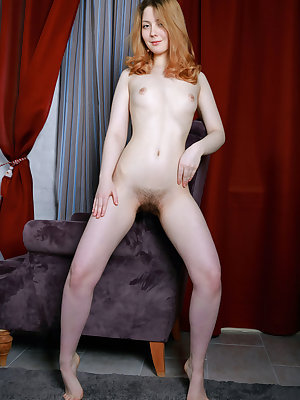 Nude solo model proudly displays her all natural vagina atop her bed spread