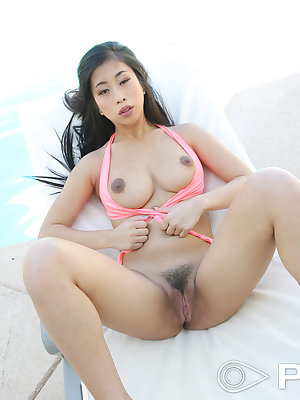 Asian solo model Jade Kush removes her pink swimsuit to pose in the nude