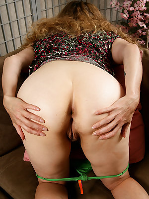 Older woman cups a boob before showcasing her hairy bush on her sofa
