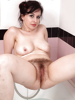 Middle aged mom Nikita putting forth her hairy pussy in the bathtub