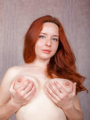 Pale redhead Sara Nikol inserts a dildo in her beaver after disrobing