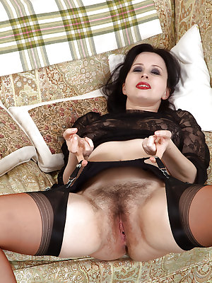 Mature brunette woman Nikita fondly showing off hairy pussy in black nylons