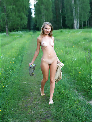 Blonde girl walks naked thru a country field before getting dressed