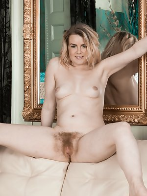 Rebecca Louise poses in her purple dress and strips it off in her living room. She moves to the couch and spreads her legs. There, her hairy pussy gets displayed and so does her total sexiness.