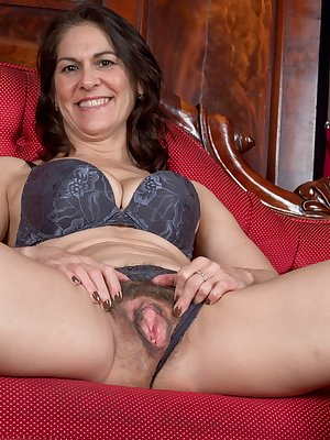 Kaysy has on an elegant dress in her red room. She takes it off with her lingerie and lays naked on her red chair. She poses with her 52 year old hairy pussy and perfect 34D breasts in full beauty.