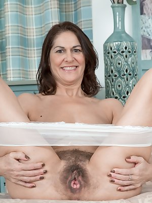 Kaysy sits in her blue blouse and grey skirt on her sofa. She strips it off with her white lingerie and lays elegantly naked. She opens her legs, opens her hairy pussy and has pink pussy lips to enjoy.