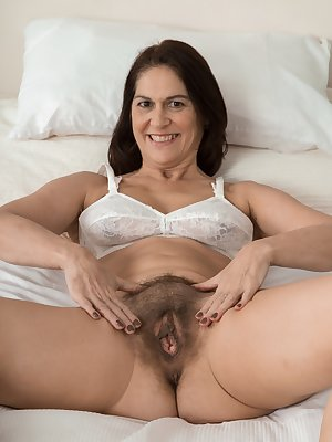 Kaysy is wearing her floral dress in her beautiful bedroom. The dress and panties that cover her hairy pussy come off. She bends over, stands up, and lays back showing the camera her hairy bush.