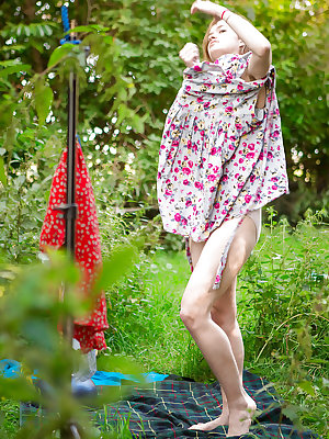 Redhead girl Laney getting dressed outdoors after nude modelling debut