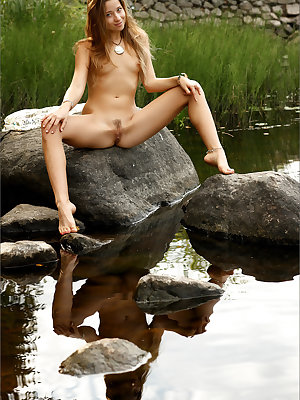 Gorgeous blonde model gets naked by the river to air her hot skinny body