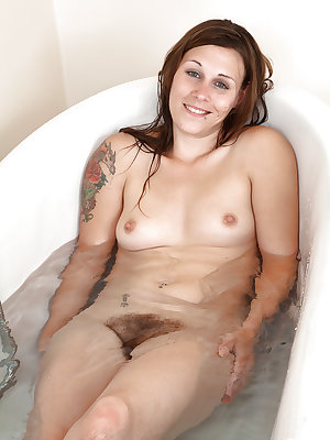 Wet mature woman with hairy legs freeing bush from bikini in bathtub