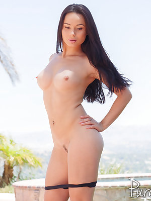 Hot older brunette Crystal Rush removes her bikini for nude poolside poses