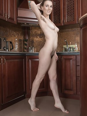Horny amateur Donatella peels off in the kitchen to oil up her hairy pussy